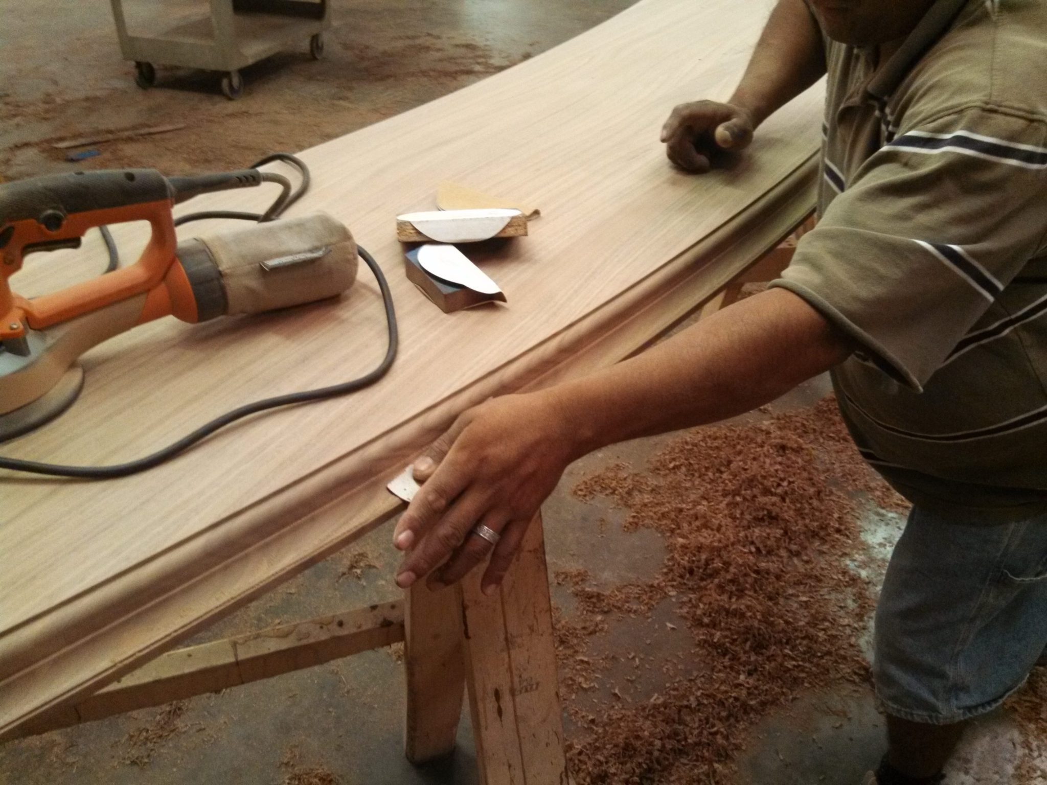 Wood bar top being hand sanded.