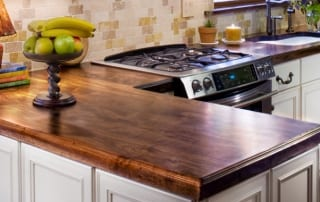 Distressed walnut countertops with gas range and undermount sink