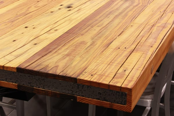 A close up of a reclaimed heart pine table top corner section.