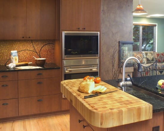 Another example of a small amount of end grain wood countertop in handy proximity to a sink set in granite.