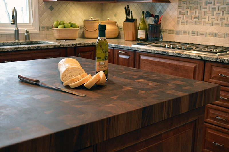 Walnut butcher block kitchen island top showing bread being cut.