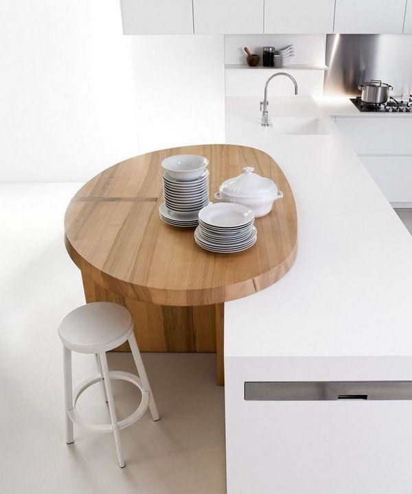 Small wood island in white kitchen.