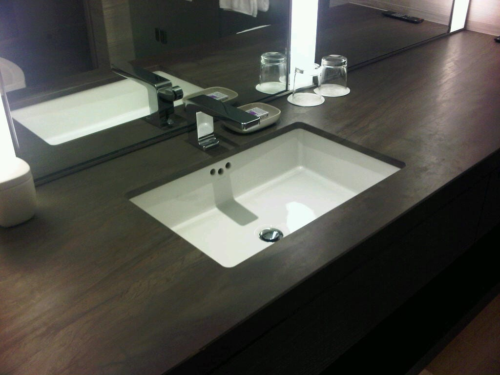 White sink in dark wood vanity