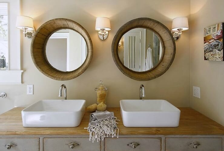 Wood vanity top with white vessel sinks and barrel mirrors